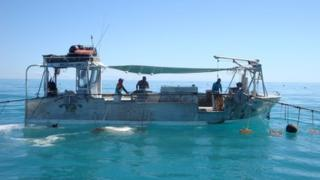 Men work on a boat in Roebuck Bay on 11 July 2012