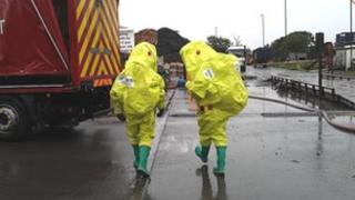 Fire crews in protective suits