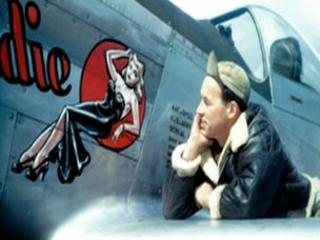 USAAF serviceman Don Allen admires nose art from the wing of a plane