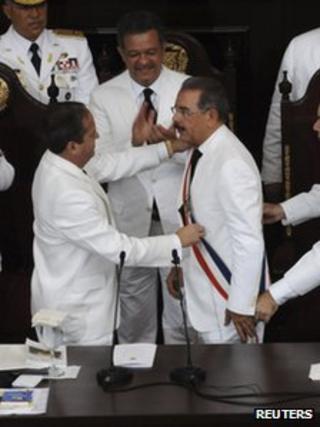 Dominican Republic's President Danilo Medina (R) receives the presidential sash from by the Senate's President Reinaldo Pared Perez