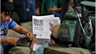 A man from India's northeastern states reads a newspaper showing news about people leaving as he waits with others to board a train home, at a railway station in Bangalore, India,Thursday, Aug. 16, 2012