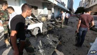 Libyan security forces inspect the remains of a vehicle near the Ministry of Interior in Tripoli early on August 19, 2012.