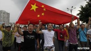 Protesters, carrying a Chinese national flag, shout slogans during an anti-Japan protest in Shenzhen, 19 Aug 2012