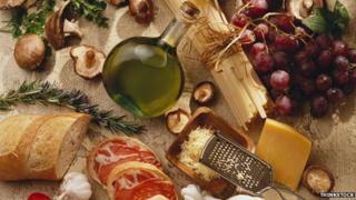 Assortment of food, including bread, olive oil, cheese, meat and grapes