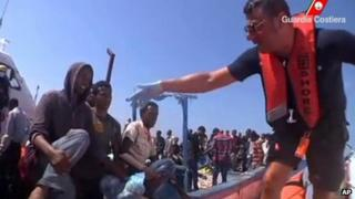 A still frame from video footage of an Italian coast guard reaching a vessel overcrowded with migrants from mainly Tunisia and sub-Saharan Africa