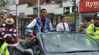 Anthony Ogogo in an open top car in Lowestoft with his Olympic medal