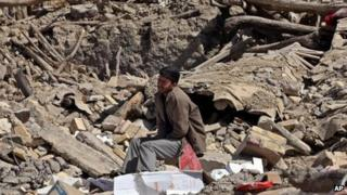 A man sits amid rubble near the village of Varzaqan in Iran's northwest Tabriz province on 11 August 2012