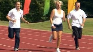 Three people running on athletics track