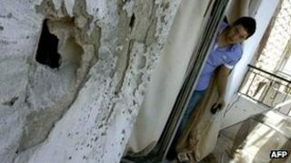 A Lebanese man looks at a hole on a building following a rocket-propelled grenade attack in the northern Lebanese city of Tripoli (22 August 2012)
