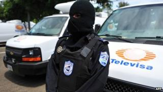 Nicaraguan police officer stands in front of confiscated vans