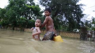 Children walking through flood water in Pathein, in the Irrawaddy delta region of Burma, 21 August 2012