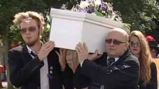 Two men carry a coffin as part of Save the Harlan Beagles' march through Cambridge