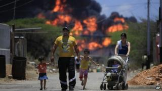 A family walks on a street as flames rise after an explosion at the Amuay refinery on 26 August, 2012