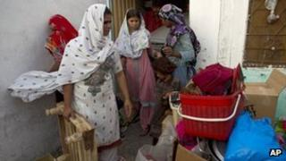 Pakistani Christian women collect their belongings to leave their home in a suburb of Islamabad, Pakistan on Thursday, Aug. 23, 2012.