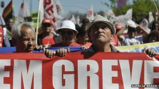 """Striking public sector workers in Brazil hold up sign saying """"On strike"""""""