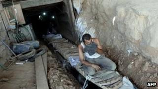 Palestinian men transport bags of cement through tunnels used for smuggling goods on 23 August