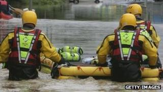 A fire rescue team with a dingy make their way down a flooded street