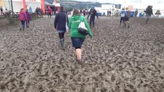 People walking in mud at festival