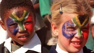 South African girls with their faces painted in the colours of the national flag, pictured in 1996, two years after the end of apartheid
