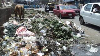Cars drive past piles of garbage in Bangalore city