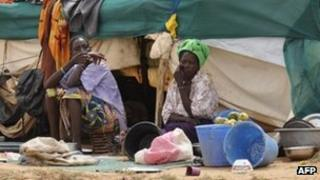 Malian refugee women sit beside a makeshift shelter on July 26, 2012, inside the Mentao refugee camp, 185 km north of Ouagadougou.