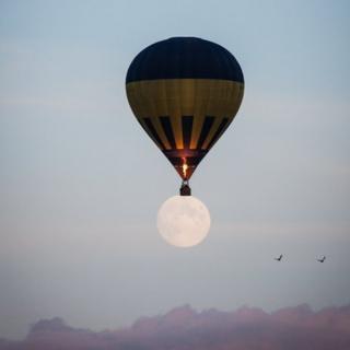 Hot air balloon over full moon