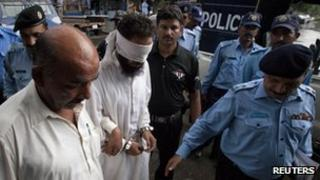 Pakistani police officers escort blindfolded Muslim cleric Khalid Chishti to appear in court in Islamabad