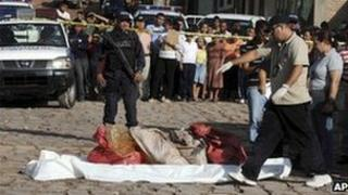 Police investigators gather bags containing body parts in the capital city of Tegucigalpa on 31 August, 2012