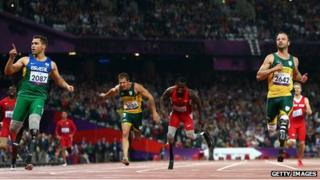 Alan Fonteles Cardoso Oliveira of Brazil crosses the line ahead of Oscar Pistorius of South Africa to win gold in the Men's 200m in 2012 Paralympics