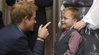Prince Harry jokes wih one of the children