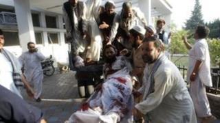 Afghan men carry a man injured in a bomb blast to a hospital in Jalalabad September 4, 2012.