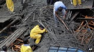 Rescuers work to remove debris after a slab of concrete from an under-construction metro bridge collapsed in Mumbai, India, Tuesday, Sept. 4, 2012.