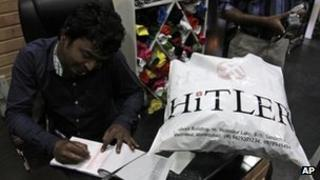 Rajesh Shah, one of the owners of the Hitler store, prepares a bill for a customer in Ahmadabad, India, Wednesday, Aug. 29, 2012.
