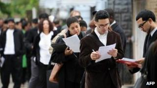 People seeking jobs wait in a line outside a job fair at a youth center to in Queens, New York on 3 May, 2012