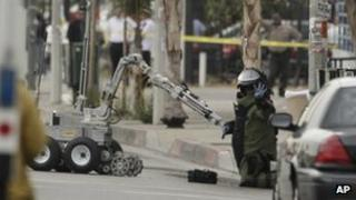 An LA bomb squad member signals after making safe the device outside the Bank of America branch in Los Angeles