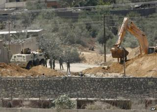 Egyptian soldiers secure the area as a bulldozer demolishes part of a smuggling tunnel on the Egyptian side of the Egypt-Gaza border, 22 August