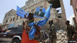"A woman holds up election campaign posters of Somalia""s President Sheikh Sharif Ahmed in Mogadishu, September 9, 2012."