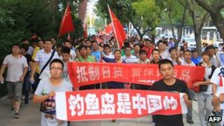People march down a street in Weihai, in eastern China's Shandong province, during an anti-Japan demonstration, 11 Sept 2012