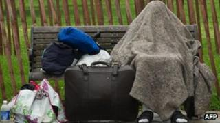 A homeless man protects himself from the rain on a bench near the White House in Washington on 14 May 2012