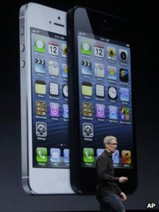 Tim Cook speaks in front of an image of the iPhone