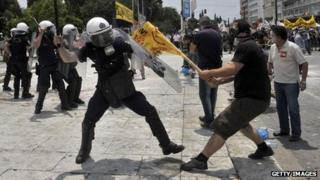 Demonstrators clash with riot police outside the Greek Parliament on June 29, 2011 in Athens during a 48-hour general strike