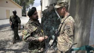 A Afghan officer from the 2nd Kandak, 2nd Brigade, 201st corps of the Afghan National Army and an officer of the 4th brigade combat team 4th infantry division of the US Army talk at Forward Operating Base Joyce, in Kunar