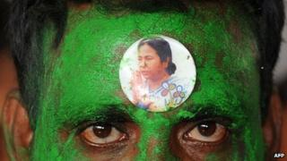 a sticker bearing a portrait of Trinamool Congress (TMC) Leader Mamata Banerjee is seen on the forehead of a supporter outside a counting centre in Kolkata