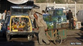 A man pulls a cart loaded with green peppers at a vegetable and fruit market in the West Bank village of Beita (12 September 2012)