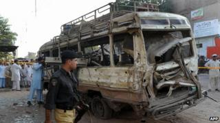 A burnt out coach in Peshawar after a bomb blast killed at least eight people on 19 September 2012