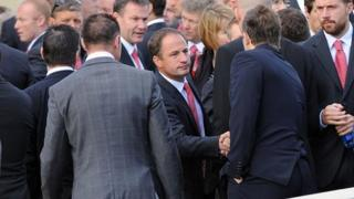 Mourners shake hands