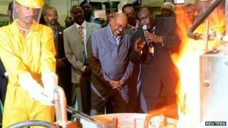 Sudan's President Omar al-Bashir (C) smiles as he looks on at the process of gold refining during the inauguration of the Sudan Gold Refinery in Khartoum, 19 September 2012