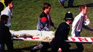 Kevin being carried on a stretcher (Image from Anne Williams)