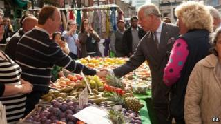 The Prince of Wales is greeted by a market trader during a visit to Surrey Street Market in Croydon, London