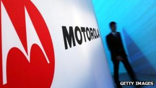 Man walks past Motorola sign